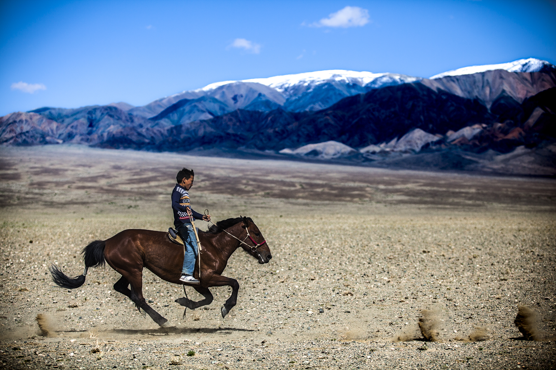 A child on horseback riding in the steppes of Mongolia