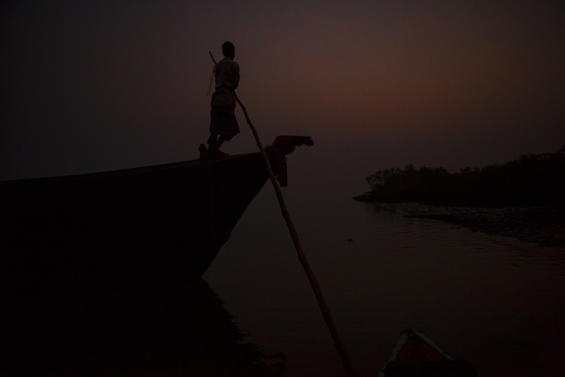 Fisherman silhouetted at dusk